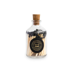 Tändstickor med svart topp i en glasburk med kork