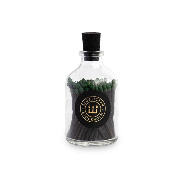 Svarta tändstickor med grön topp i en glasburk med kork