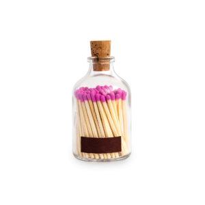 Tändstickor med rosa topp i en glasburk med kork