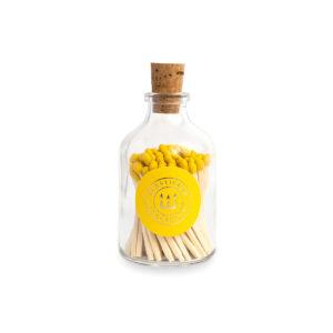 Tändstickor med gul topp i en glasburk med kork