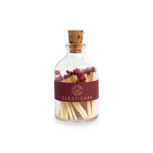 Tändstickor med vinröd topp i en glasburk med kork