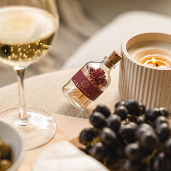 tändstickor med vinröd topp i en vacker glasburk med kork