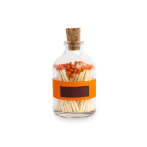 Tändstickor med orange topp i en glasburk med kork