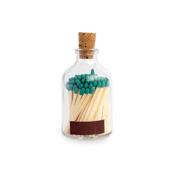 Tändstickor med turkos topp i en glasburk med kork