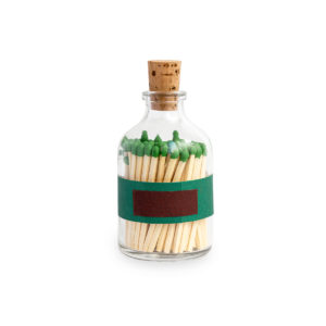 Tändstickor med grön topp i en glasburk med kork