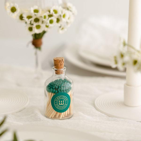 tändstickor med turkos topp i en vacker glasburk med kork