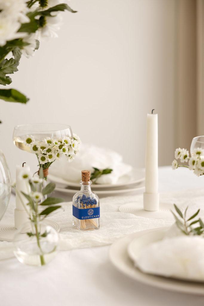 Liten Hav på ett dukat bord med blommor och ljus